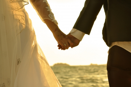 married together: Young adult male groom and female bride holding hands on beach at sunset.