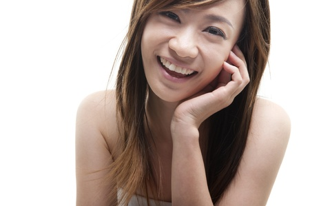hand on chin: Cute Asian female smiling on white background