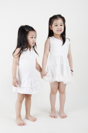 innocent: Asian sisters holding hand on plain background