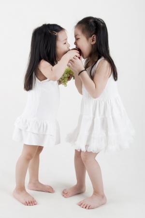 niños chinos: Dos niñas comparten una manzana