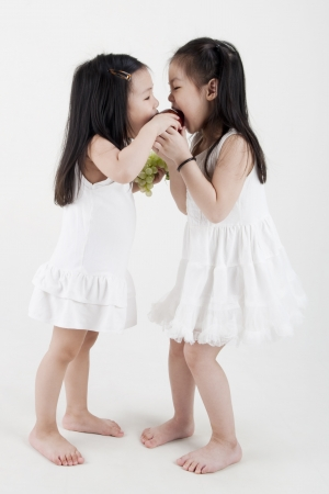Two little girls sharing an apple photo