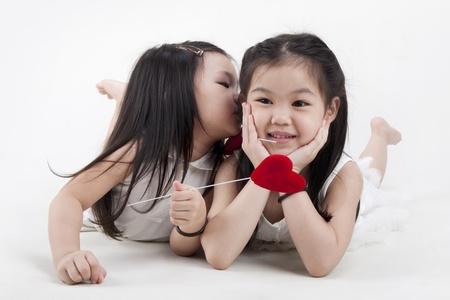 affectionate action: Ni�a besando a su hermana