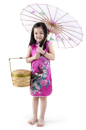 niños chinos: Niña oriental en cheongsam tradicionales vestidos chinos con sombrilla y canasta