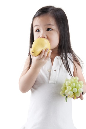 Little Asian girl eating pear and grapes, on white background photo