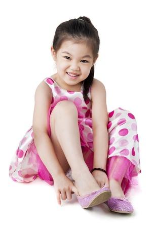 assis par terre: Petite fille de mettre sur sa chaussure