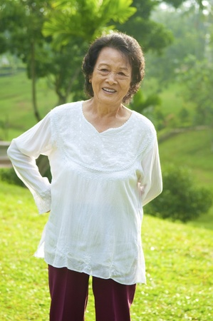 80s Asian senior woman back pain after exercise in the park at morning photo