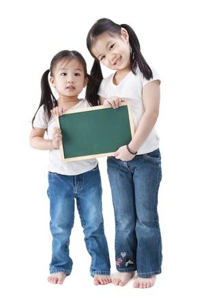 asian toddler: Happy smiling Asian girls holding blank blackboard, on white background.