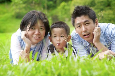 Asian outdoor family lying on green field photo