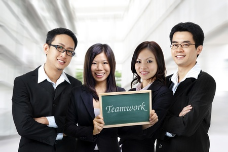Asian business team on office background, blackboard on hand. photo