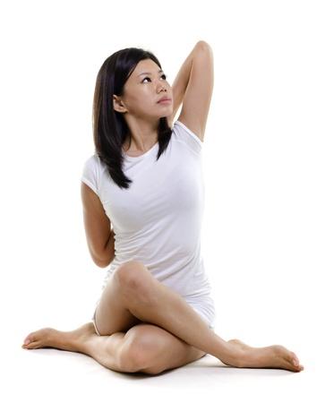 cross leg: Mujer en el yoga, la postura de la vaca (Gomukhasana), en el fondo blanco Foto de archivo
