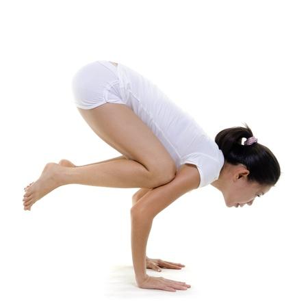 woman posture: Woman in yoga, Crane Posture (Bakasana), on white background Stock Photo