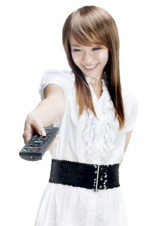 Young woman holds out a remote control to change television stations. photo