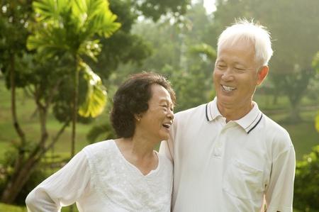 actief luisteren: Aziatische Senior paar dat gesprek bij outdoor park Stockfoto