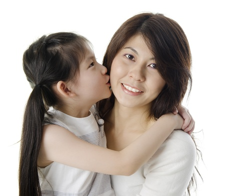 Happy Asian daughter kissing her mother on white background Stock Photo