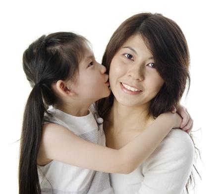 madre con hija: Hija feliz de Asia besa a su madre sobre fondo blanco Foto de archivo