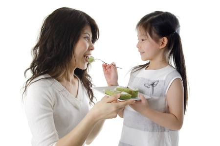 Little Asian girl feeding cake for her mother photo