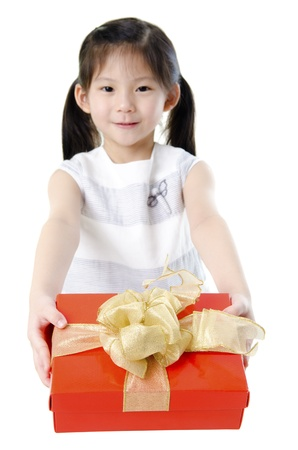 Little Asian girl arms out holding a beautiful wrapped present. Focus is on the ribbons. Stock Photo - 11219179