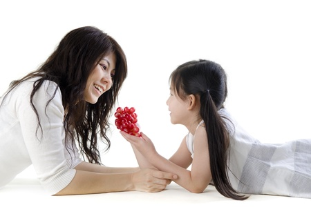 Mother and daughter sharing grapes on white background photo