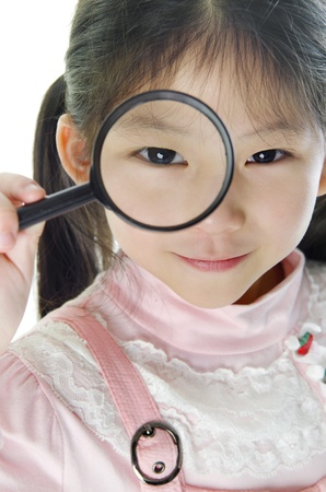 A little girl peers at the camera through a magnifying glass.