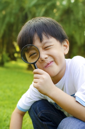 explore: Little boy exploring nature by magnifier