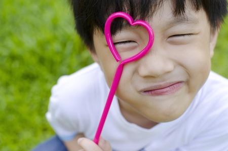 Cute Asian boy holding a heart shape on his eye photo