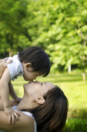 healthy asian family: Outdoor park mother kissing son