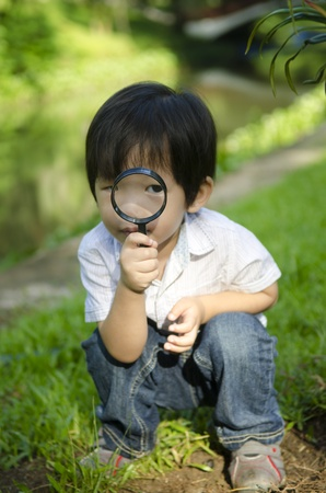 Little boy exploring nature by magnifier Stock Photo - 11539659
