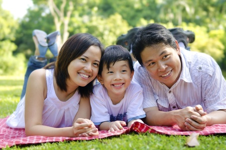 happy asian family: Outdoor happy Asian family lying on floor Stock Photo
