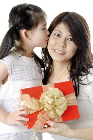 Little Asian girl giving gift for mother and kissing on mother's cheek photo