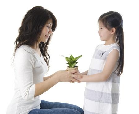educazione ambientale: Madre e figlia asiatico prendersi cura di piante