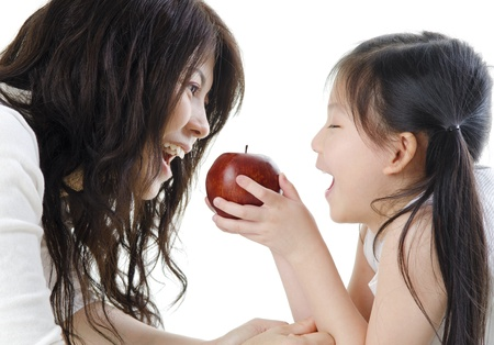 Mother and daughter sharing an apple on white background photo