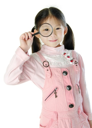 A little girl peers at the camera through a magnifying glass. photo