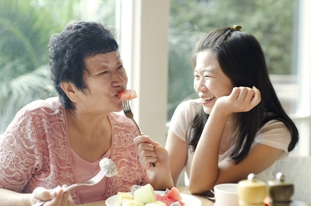 Asian adult daughter feeding fruit to senior mother photo