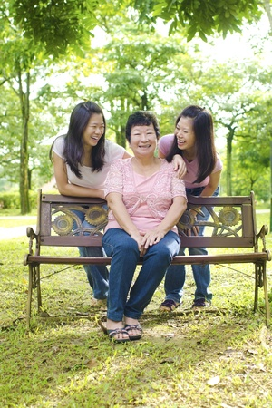 mother on bench: Happy Asian senior mother with her daughters