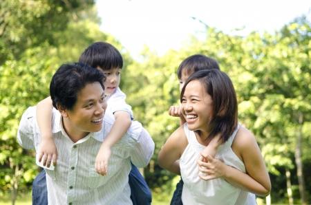 shoulder ride: Familia asi�tica feliz que se divierte en un agradable d�a de verano.
