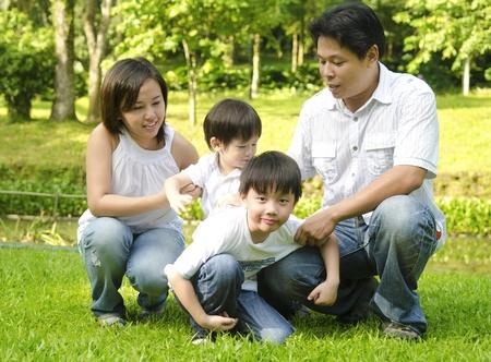 en cuclillas: Familia asiática feliz divirtiéndose en el parque al aire libre
