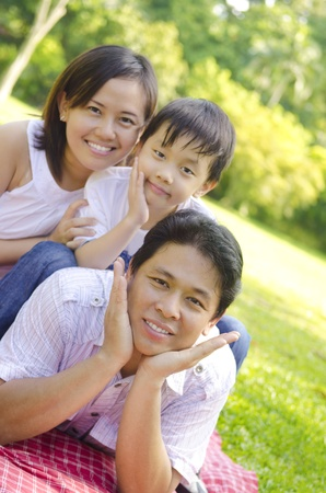 outdoor living: Asian family lying outdoors smiling