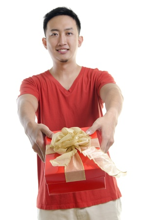 Asian young man giving a gift box on white background