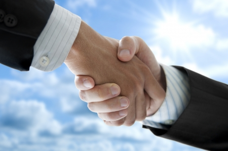 black handshake: Businessmen shaking hands over blue sky, low angle view. Stock Photo