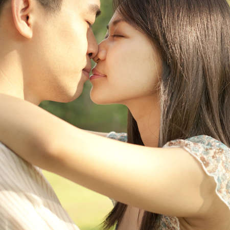 Young Asian couple kissing at outdoor photo
