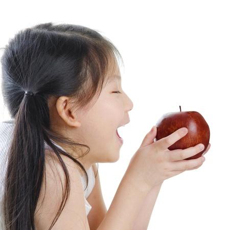 little girl eating: Asian girl holding an apple on white background