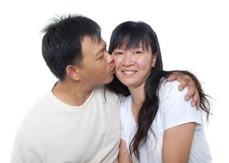 Loving Mature Asian couple kissing on white background photo