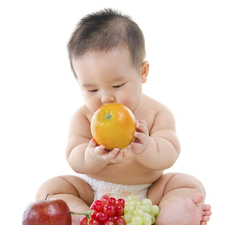 regordete: Pan Asi�tica Vegetariana beb� jugando con frutas sobre fondo blanco