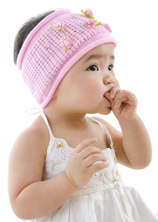 Cute pan Asian baby girl eating on white background photo