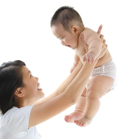 madre y bebe: Madre asi�tica jugando con su beb� Foto de archivo