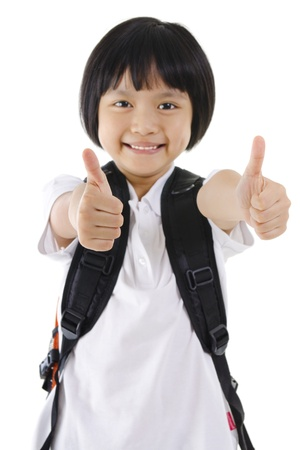 Thumbs up primary school girl with backpack on white background Stock Photo