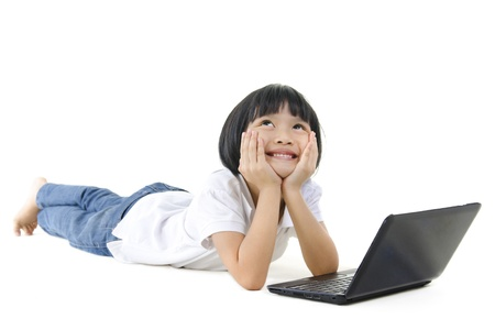 Pan Asian school girl using laptop and looking up Stock Photo - 13011335