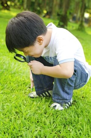 拡大鏡で自然を探索の小さな男の子