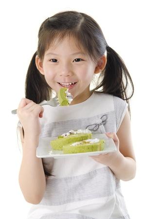 Little Asian girl is enjoying her dessert photo