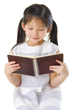 Little Asian girl reading on white background photo